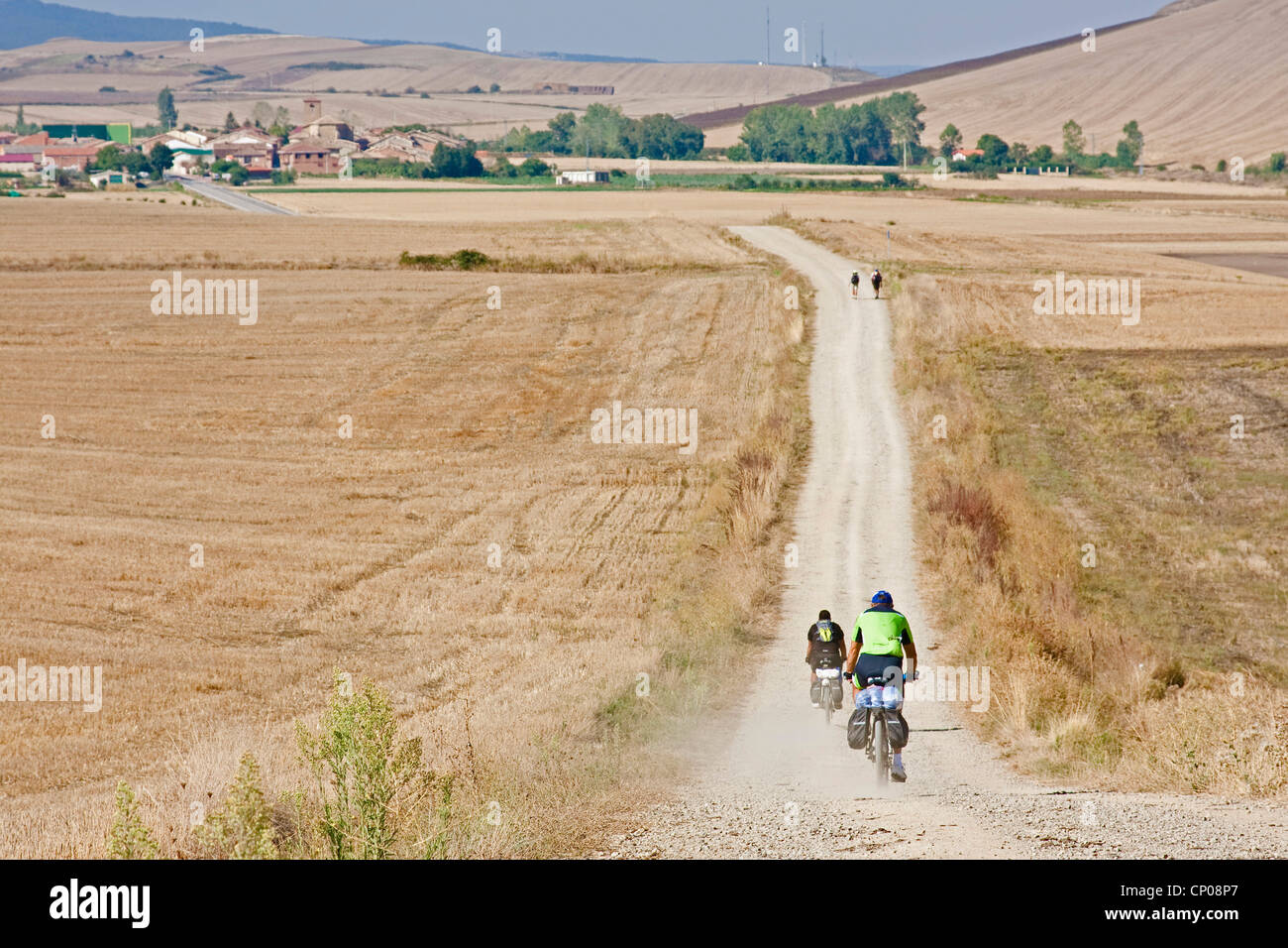 pilgrims on the Way of St. James biking or walking through stubble fields between Gra��n and Redecilla del Camino, Stock Photo