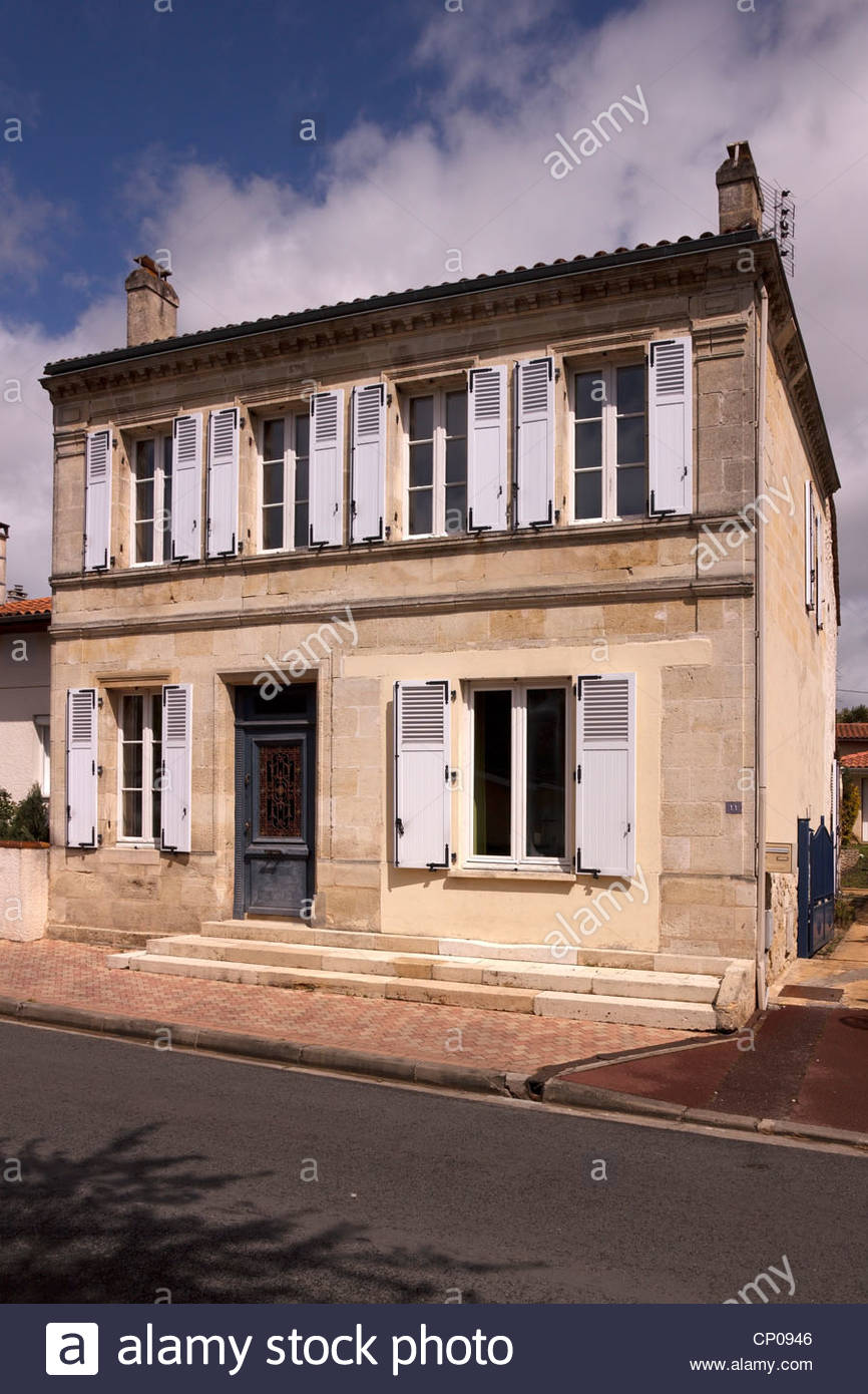 Attractive stone french house with open window shutters in Caychac, Blanquefort, Bordeaux, Aquitaine, France - Stock Image