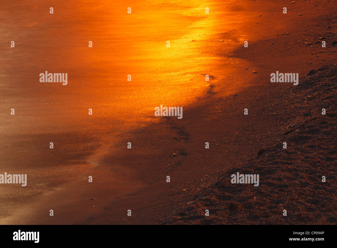 Golden reflection of setting or rising sun in water on shoreline. - Stock Image