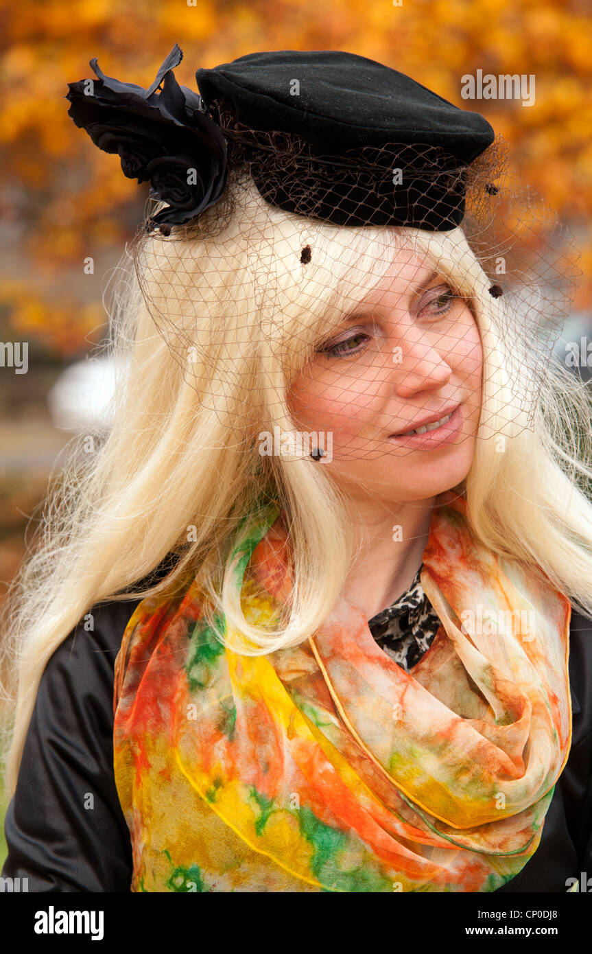 attractive woman in a fashionable hat against the autumn landscape Stock Photo