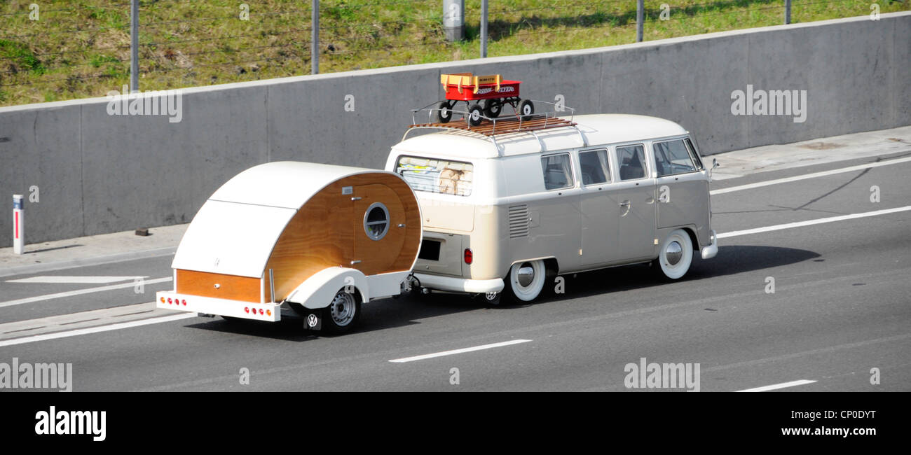 VW RV campervan motorhome with roof rack towing Teardrop Micro trailer type camper caravan along M25 motorway Essex - Stock Image