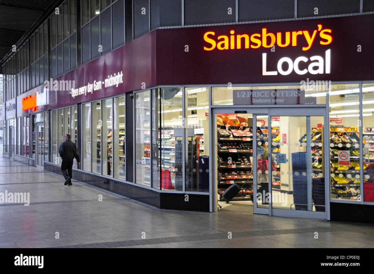 Early morning view of Sainsburys Local supermarket convenience store shop front adjacent to Euston train station - Stock Image