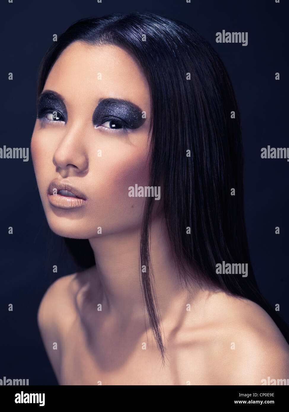 Artistic beauty portrait of an asian woman with sparkling black eyeshadows isolated on dark background - Stock Image