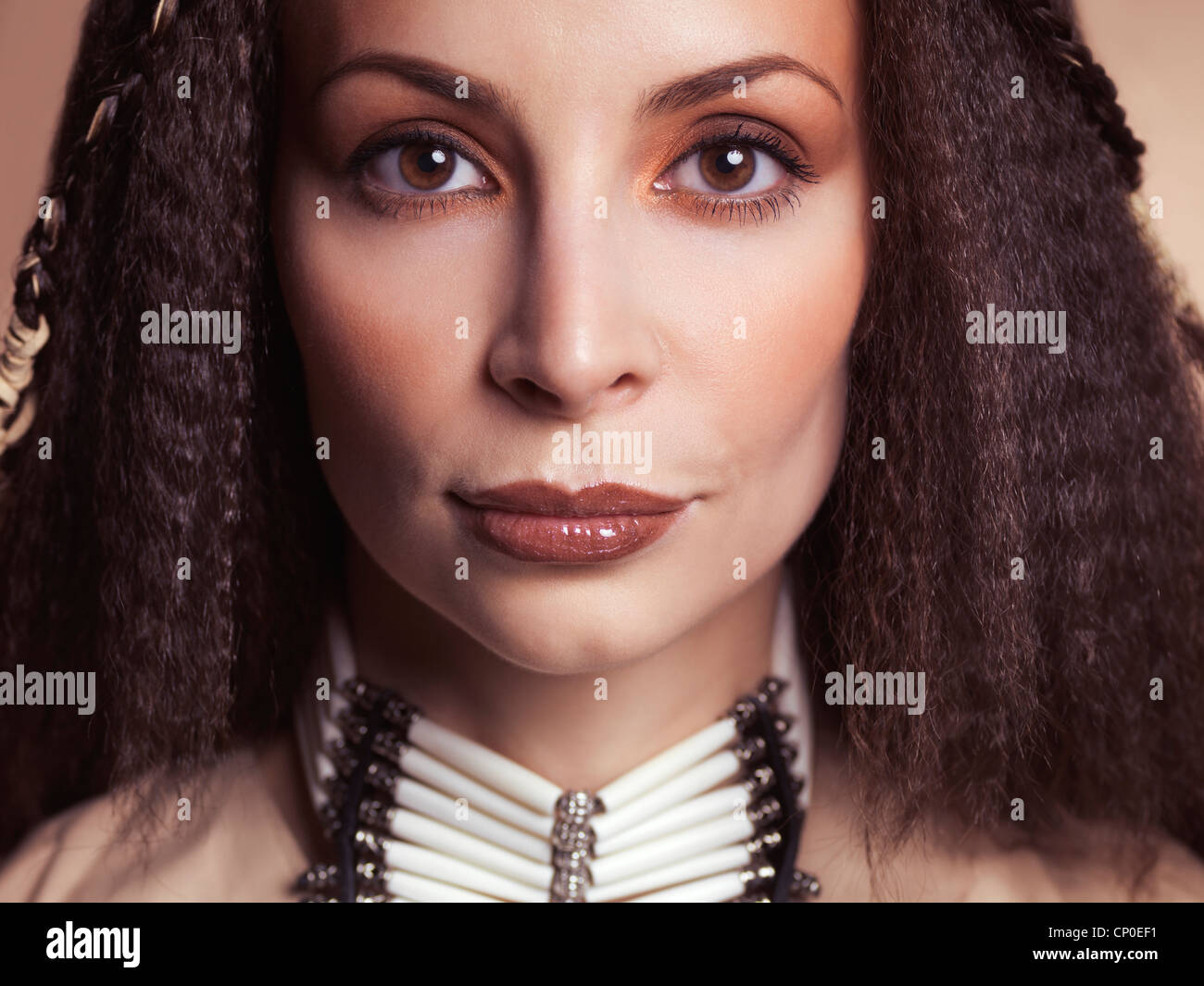 Closeup beauty face portrait of a beautiful woman wearing native accessories - Stock Image