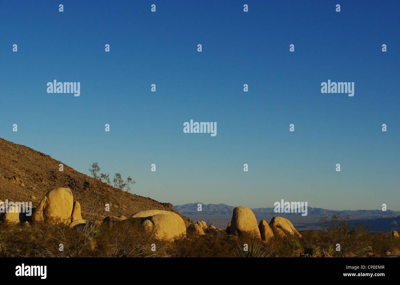 Beautiful rocks in evening light with vast desert view, Joshua Tree National Park, California - Stock Image