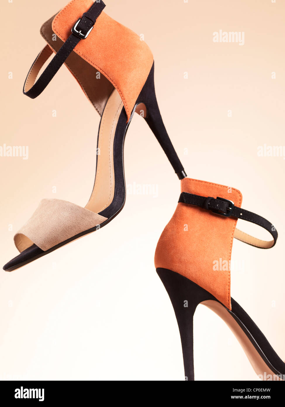 Artistic still life of a pair of fancy open-toe high heel shoes isolated on beige background - Stock Image