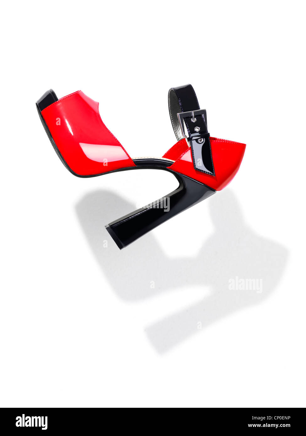 Trendy red with black high heel platform shoe falling through the air isolated on white background - Stock Image