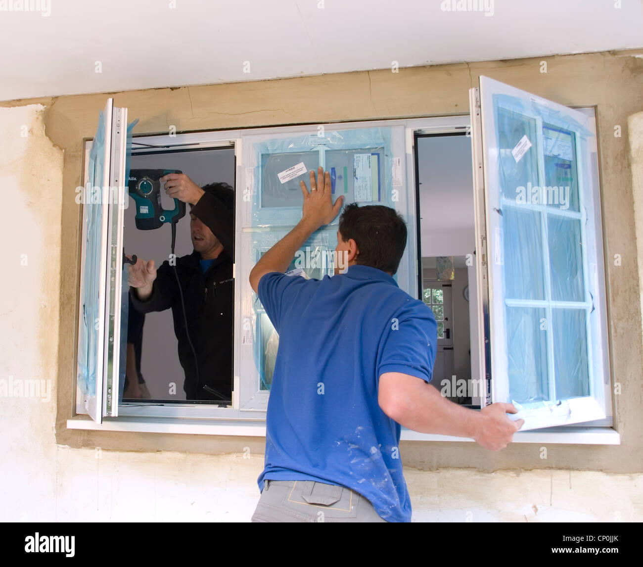 Installing A rated energy efficient replacement double glazed windows on a house extension. - Stock Image