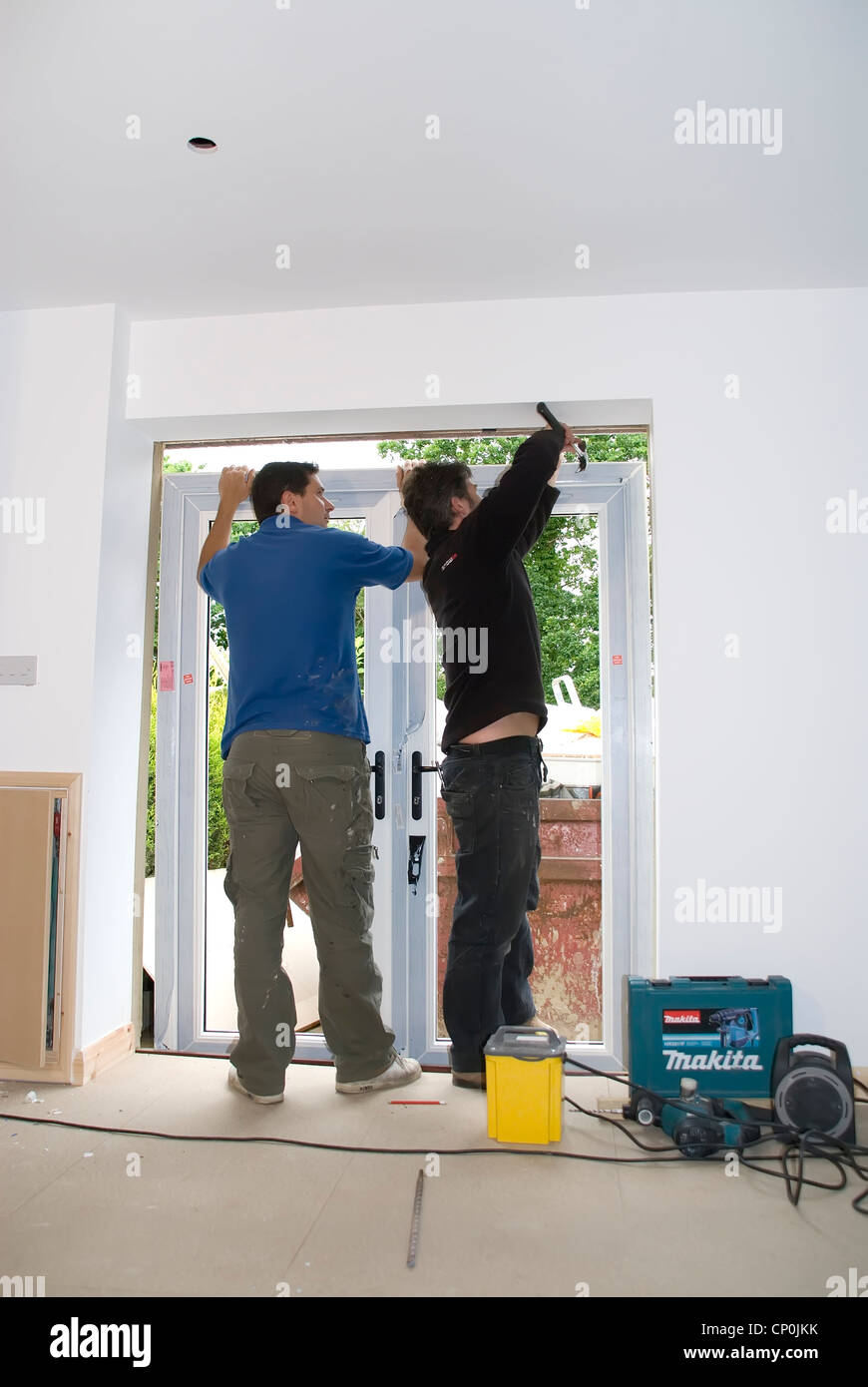 Installing A rated energy efficient replacement double glazed Fench windows doors in a garage conversion house extension. - Stock Image