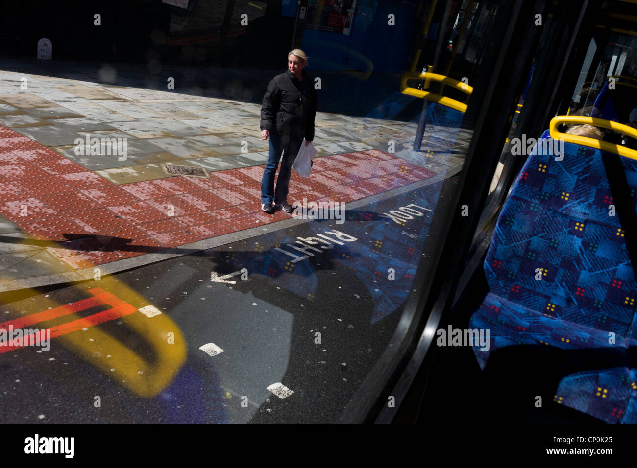 Lonely looking woman standing at the kerbside on a London street, seen from a travelling commuter bus. - Stock Image