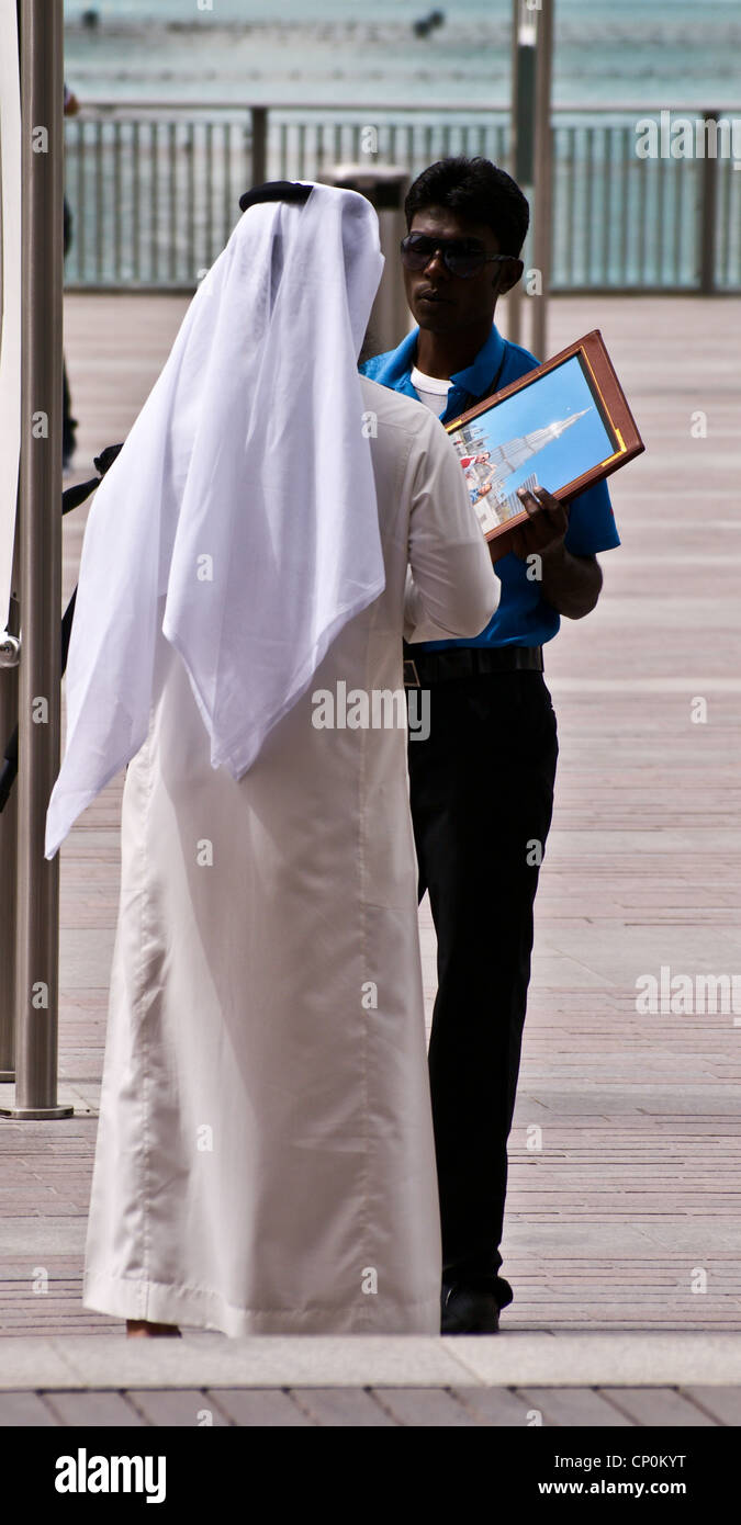 8154401aa Photographer selling photograph of the Burj Khalifa to man in traditional Arab  dress