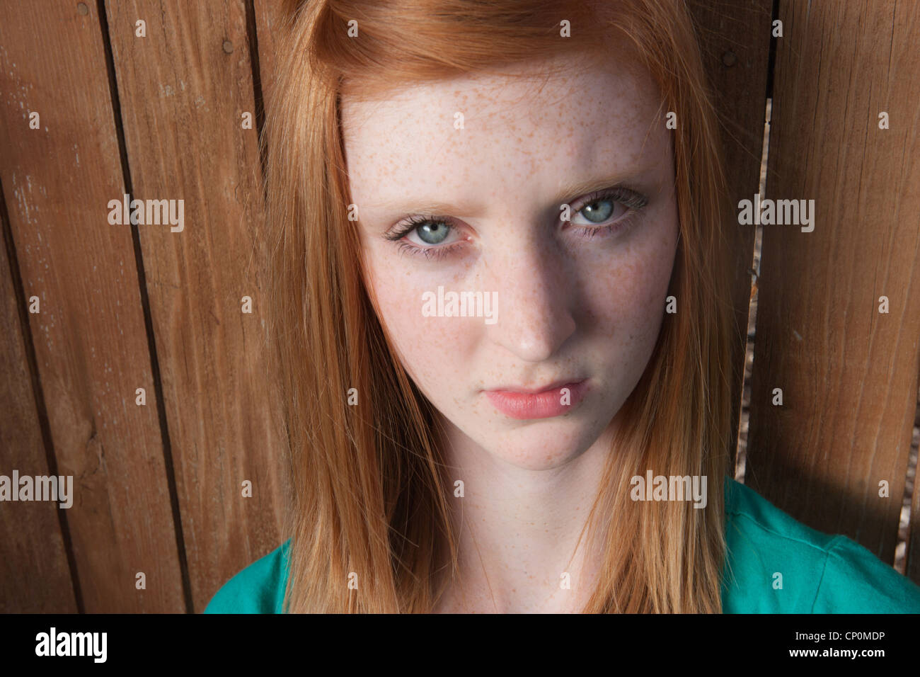 Fifteen year old girl with red hair and green eyes looks at camera with upset expression. - Stock Image