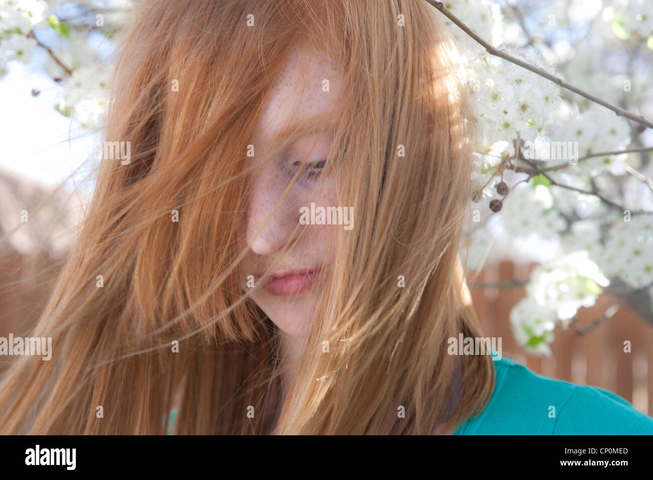 Red Haired Teenage Girl Looks Down With Hair Flowing In Front Of Her