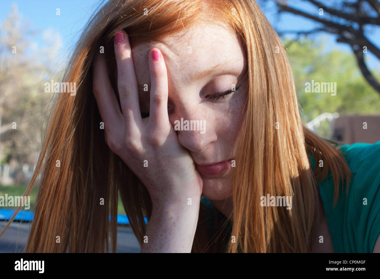 Close up of sixteen year old teen girl with hand on her face. - Stock Image