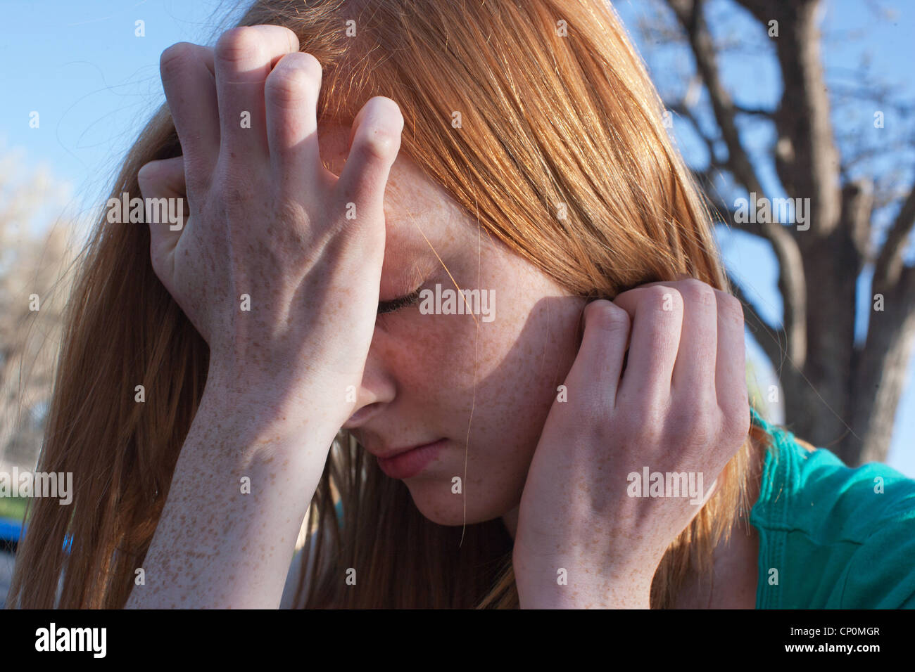 Close of a sixteen year old girl experiencing anxiety and covering her face with her hands outdoors. - Stock Image