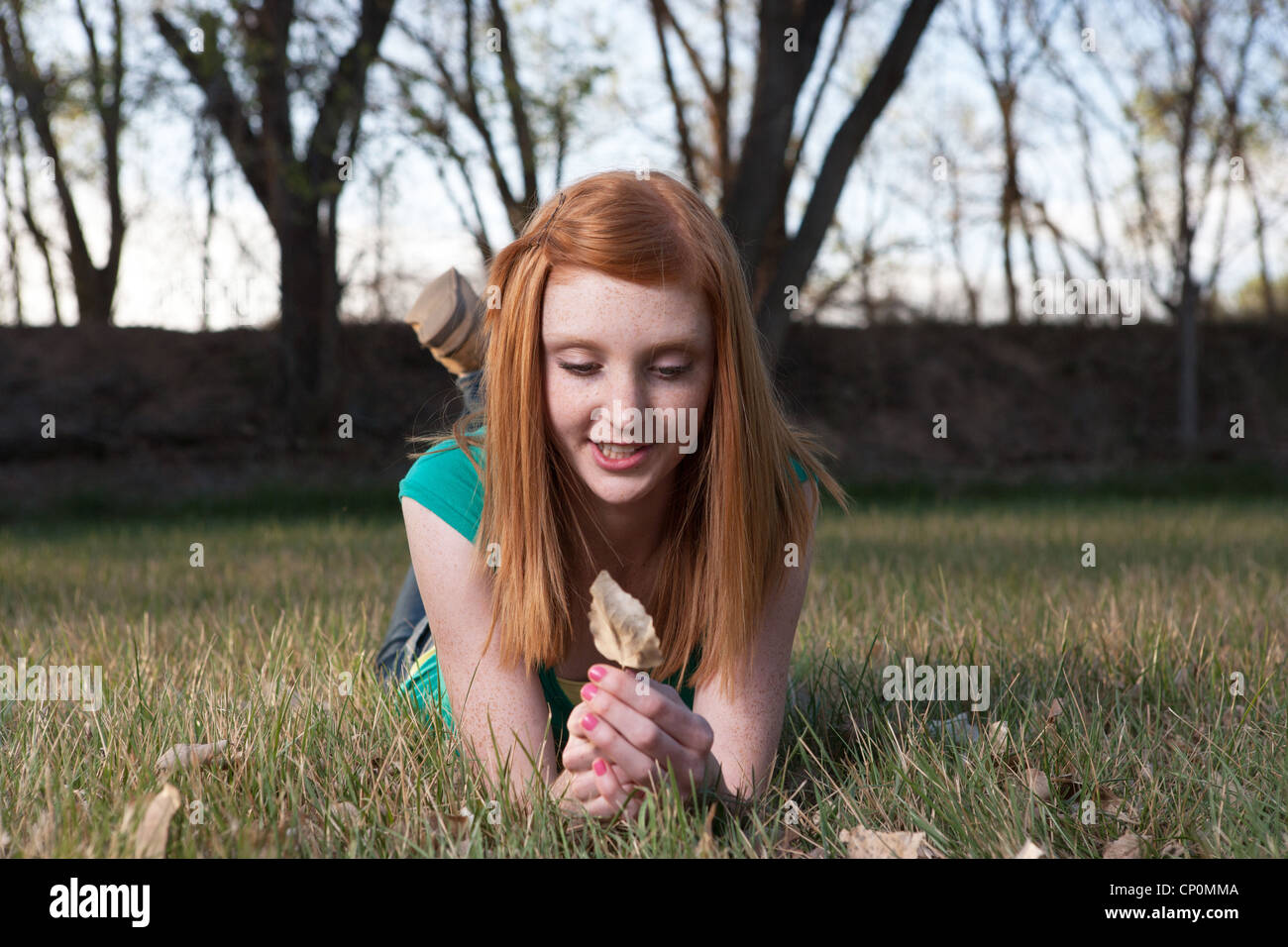 Pretty fifteen year old girl with red hair holding leaf in a field - Stock Image