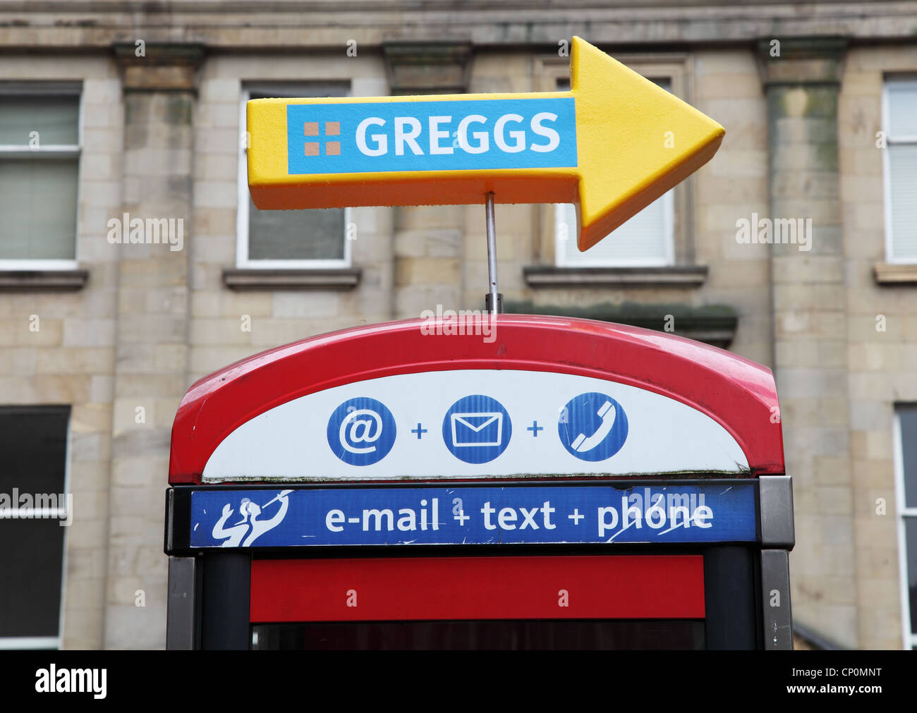 Sign, above telephone kiosk, pointing to Greggs the bakers Newcastle upon Tyne, England, UK - Stock Image