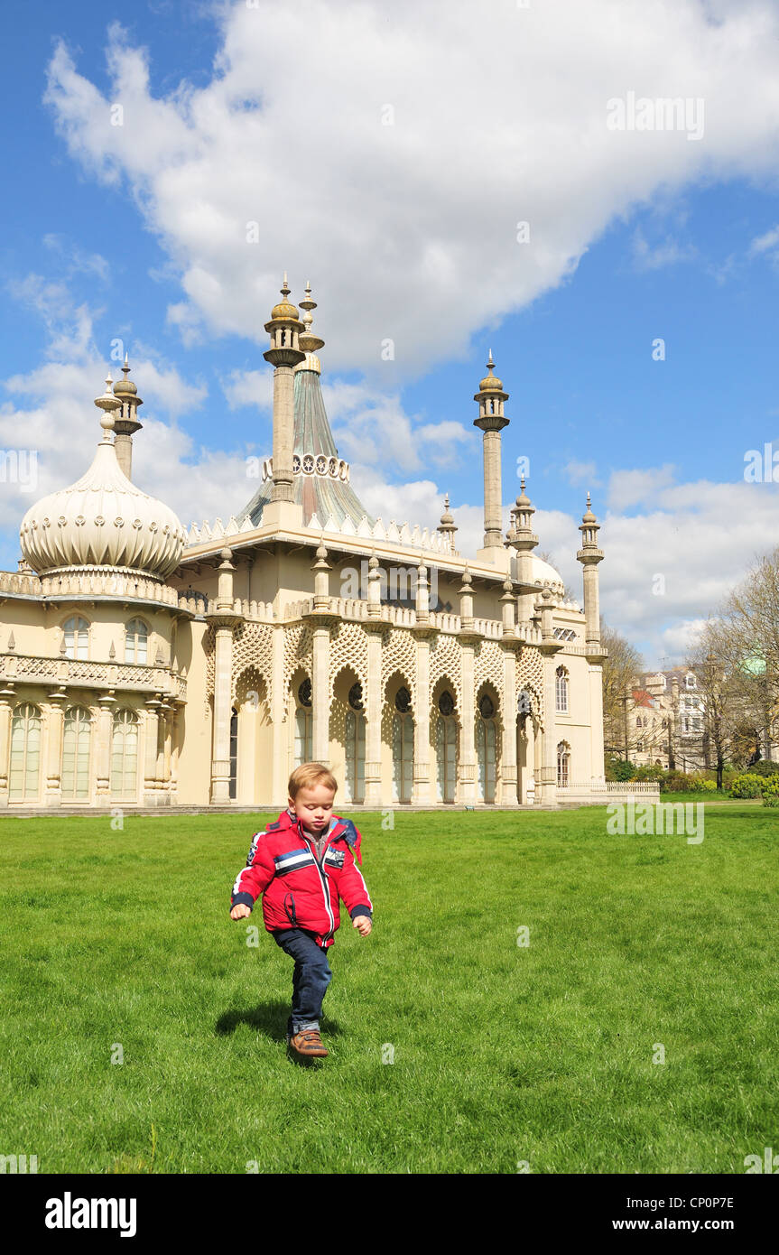 A little boy in the Brighton Pavilion gardens with the Brighton Pavilion in the background - Stock Image