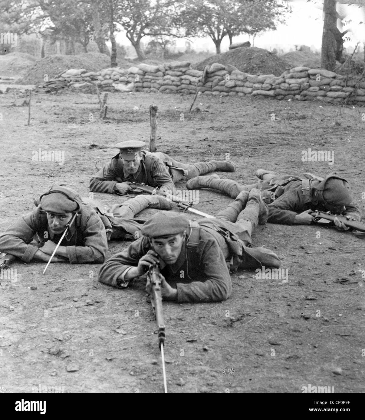 Four soldiers with rifles lying on ground, during World War One - Stock Image