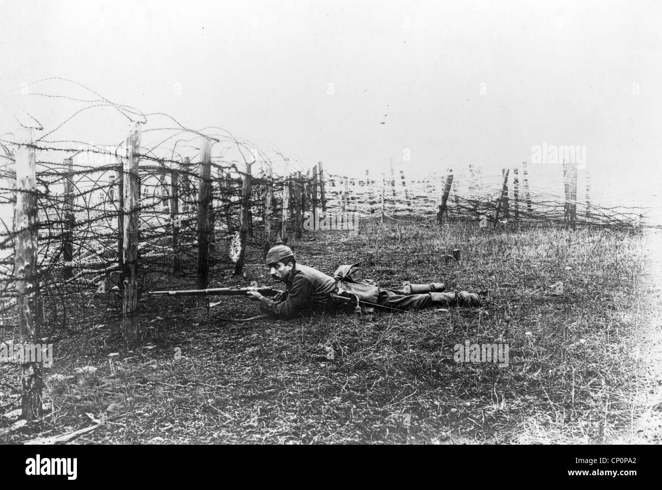 German sniper laying on ground near barbed wire defenses, World War One - Stock Image