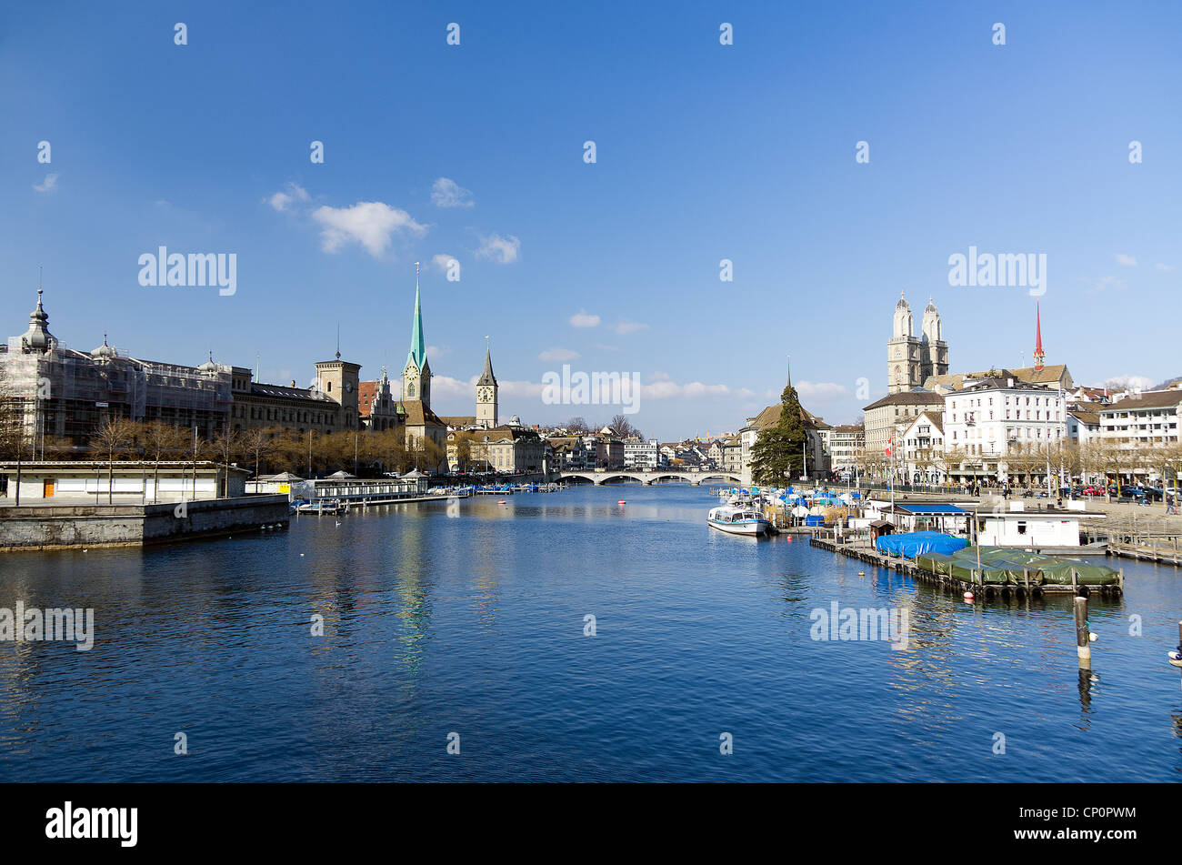 Zurich downdown in broad daylight with churches, river and boats - Stock Image