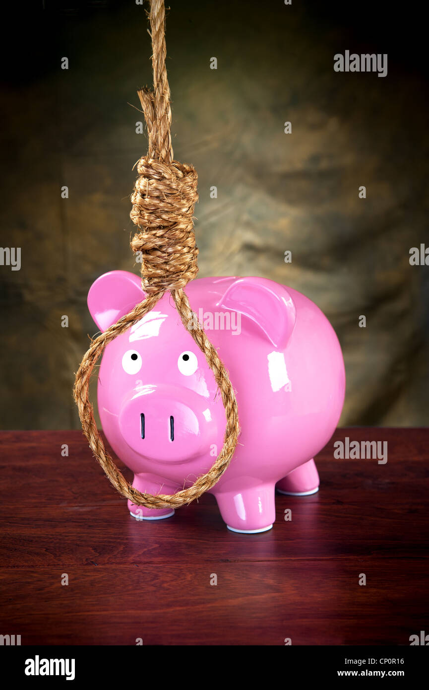 A pink piggybank against a dark, moody background prepared to hang himself with a noose. - Stock Image