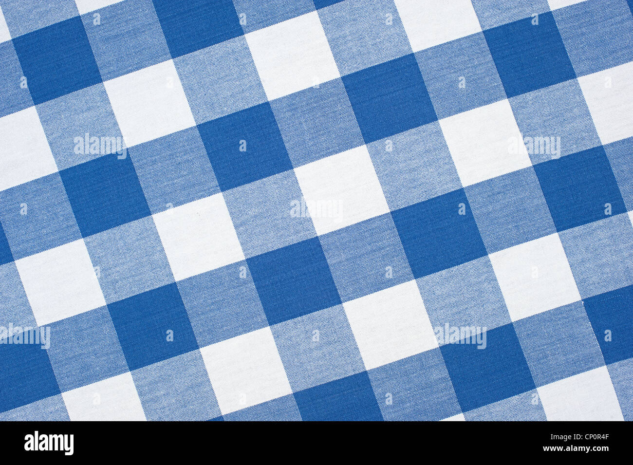 A blue, seamless, checkered picnic tablecloth fully framed with a diagonal perspective. - Stock Image