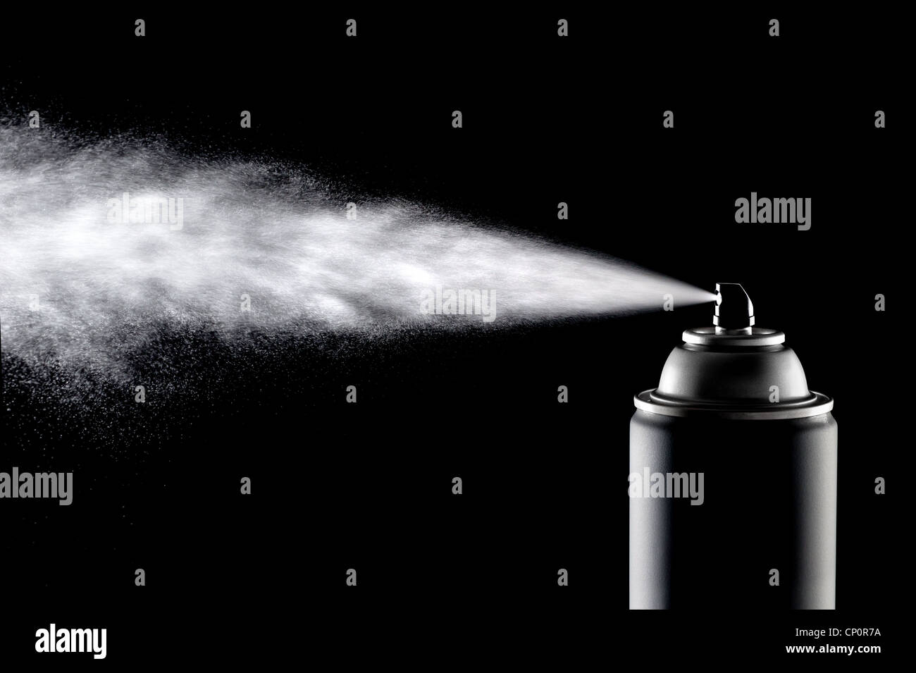 An aerosol can of spray dispensing its content against a backlit black background. - Stock Image