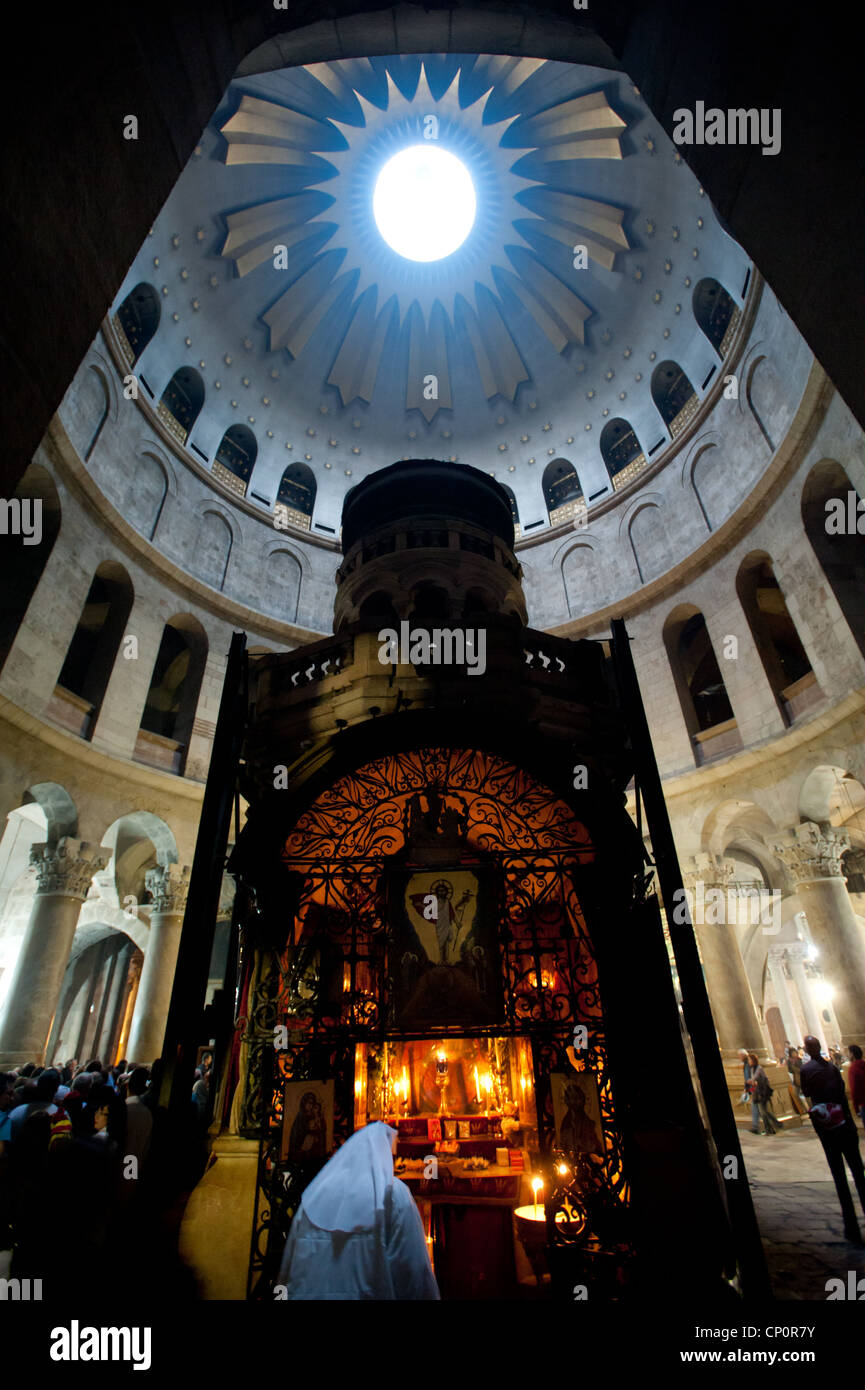 Candles illuminate a shrine in the Church of the Holy Sepulchre, holy site of the crucifixion, burial, and resurrection - Stock Image