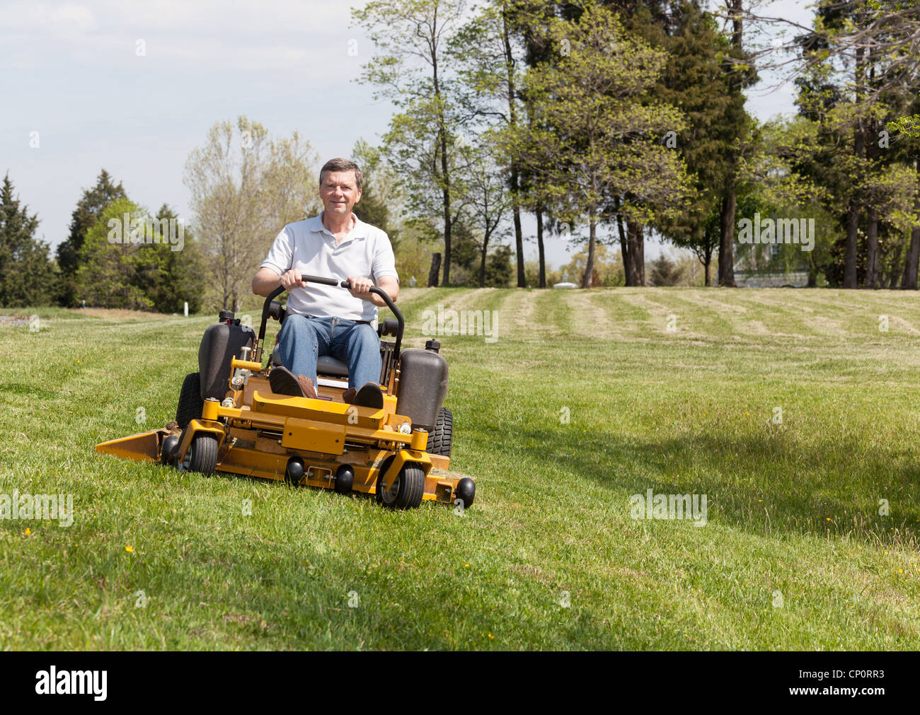 Senior retired male mowing the lawn and cutting the grass on a large lawn using yellow zero-turn ride on lawnmower - Stock Image