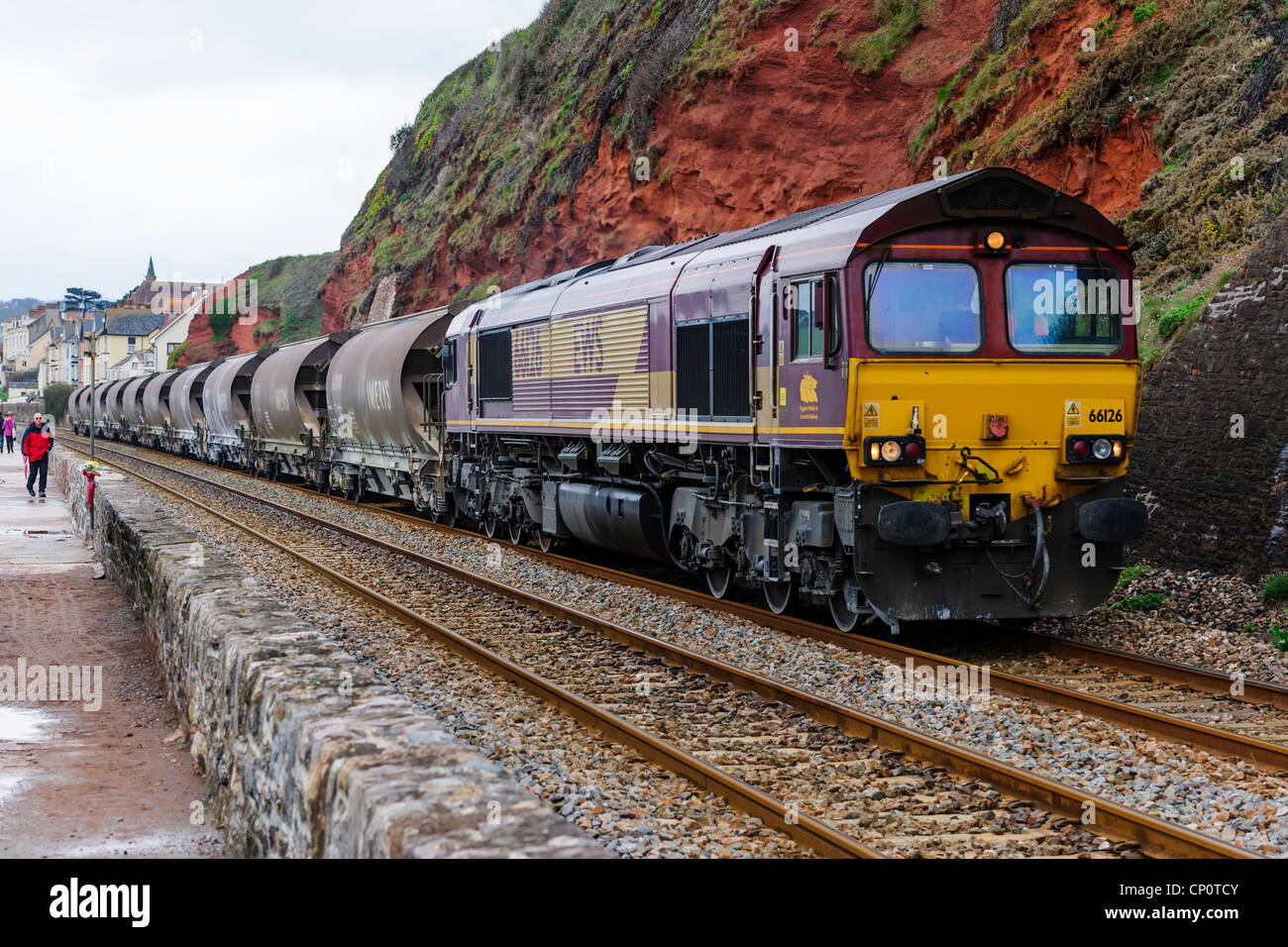 DBS Class 66/0 diesel locomotive 66126 hauls a freight train along the sea wall Dawlish south Devon UK - Stock Image
