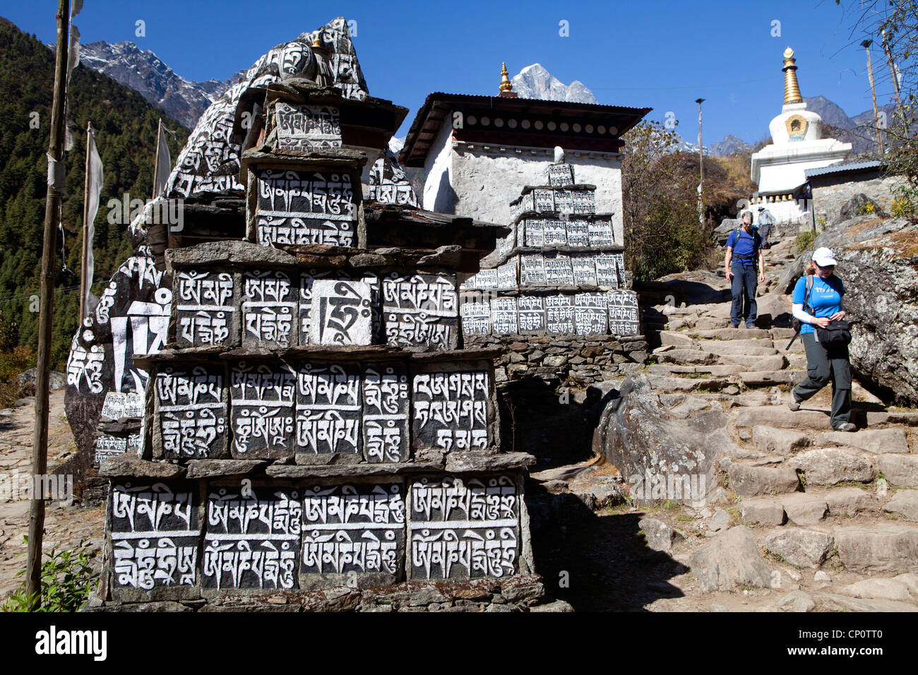 Trekking past a mani wall along the trail to Everest Base Camp - Stock Image