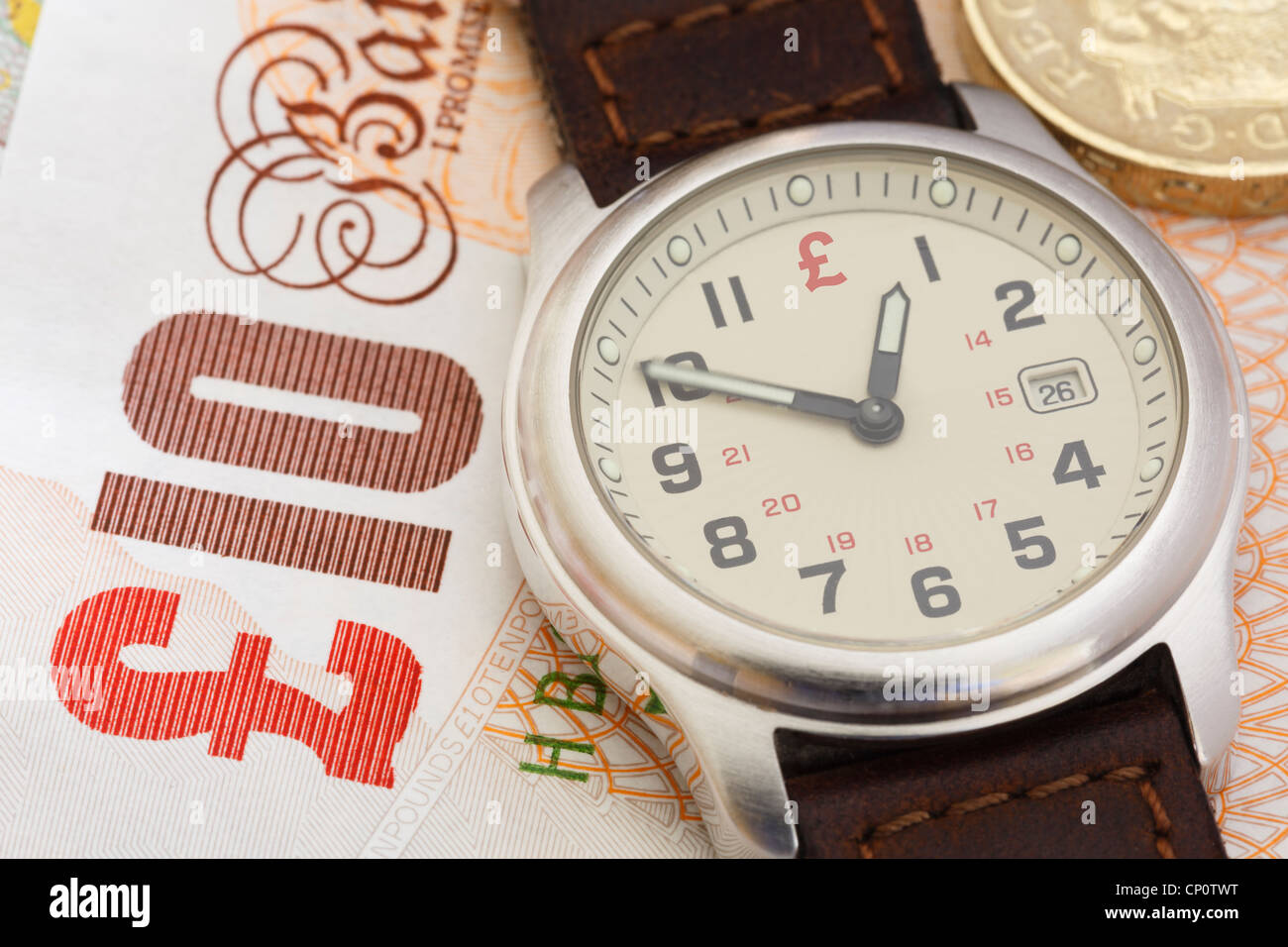Wristwatch clock on a Sterling ten pound note and a pound coin to illustrate financial concept time is money in Stock Photo