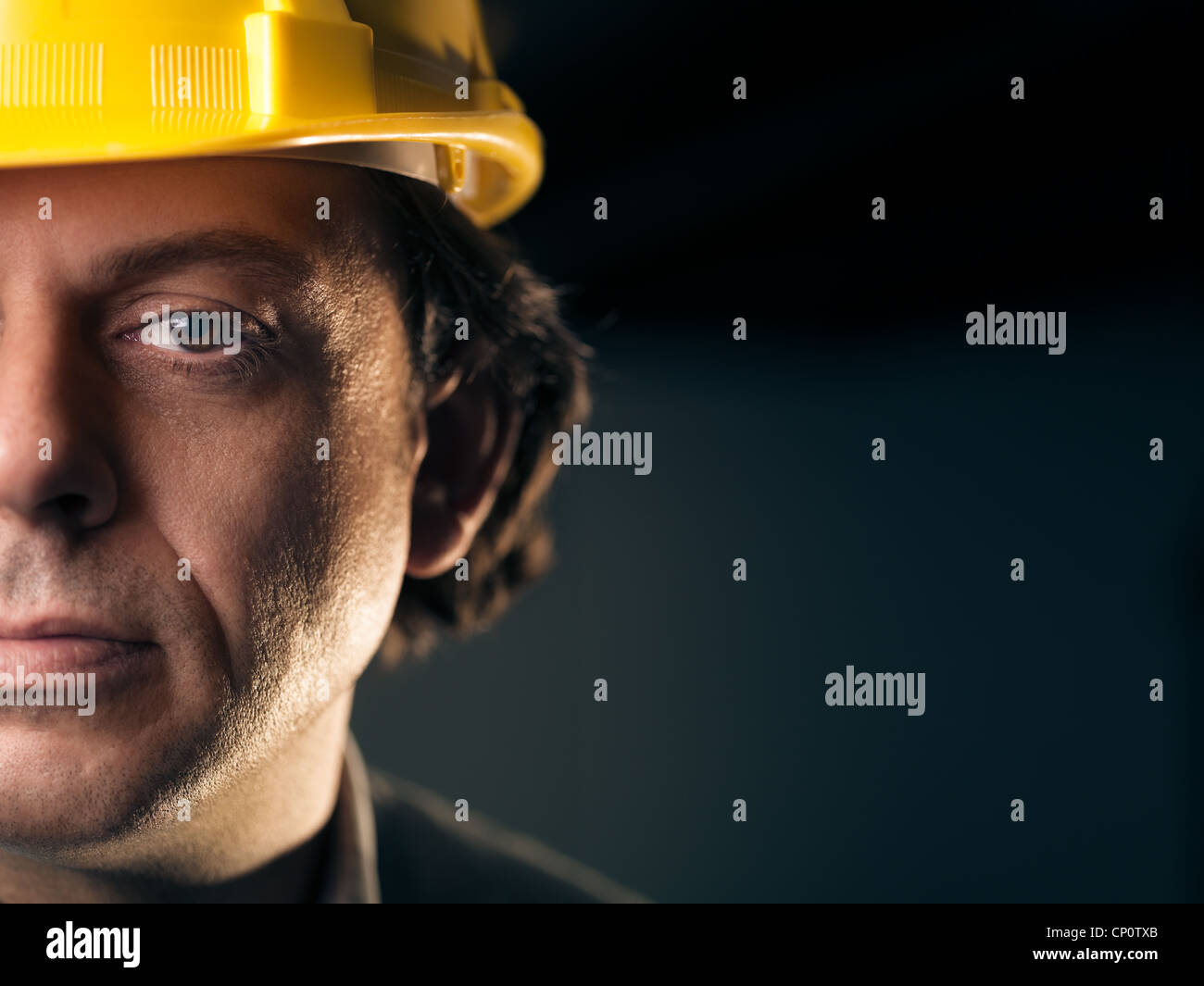 Portrait of serious middle aged man working as construction worker with hardhat. Copy space - Stock Image