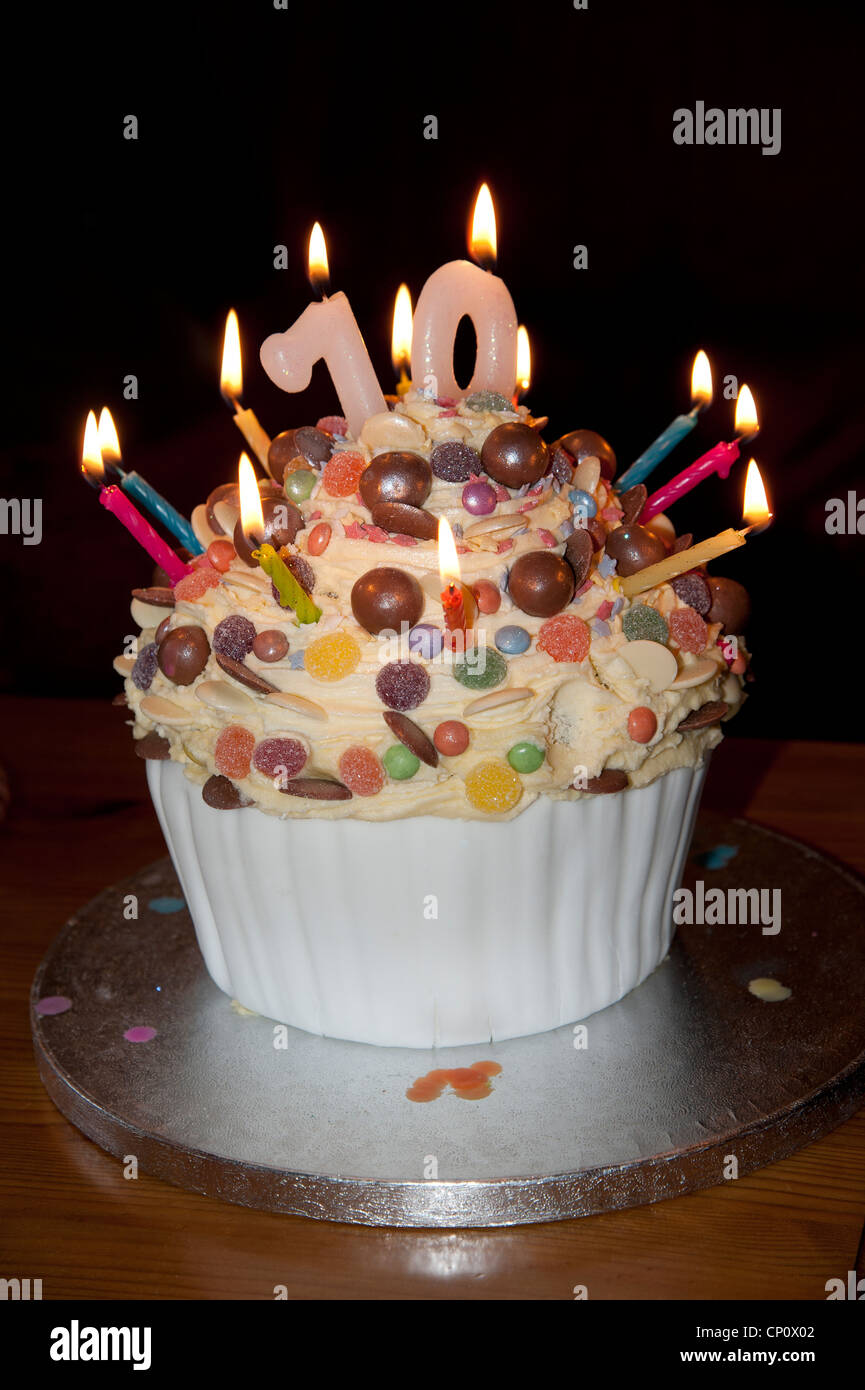 70th Birthday Cake With Lighted Candles And Decorated Sweets