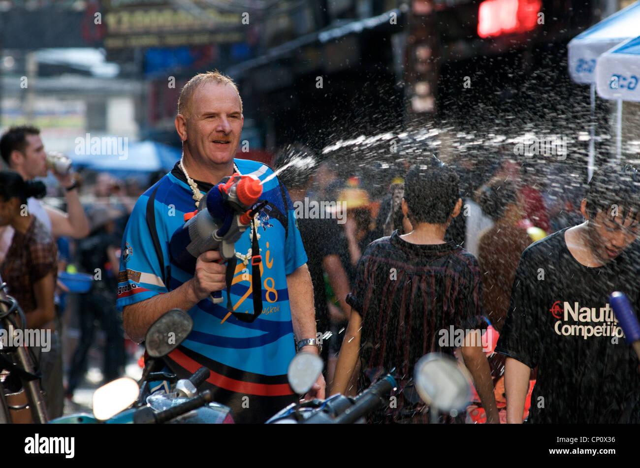 Tourist w/ water gun during Songkran. Bangkok, Thailand on April 15th, 2012. - Stock Image