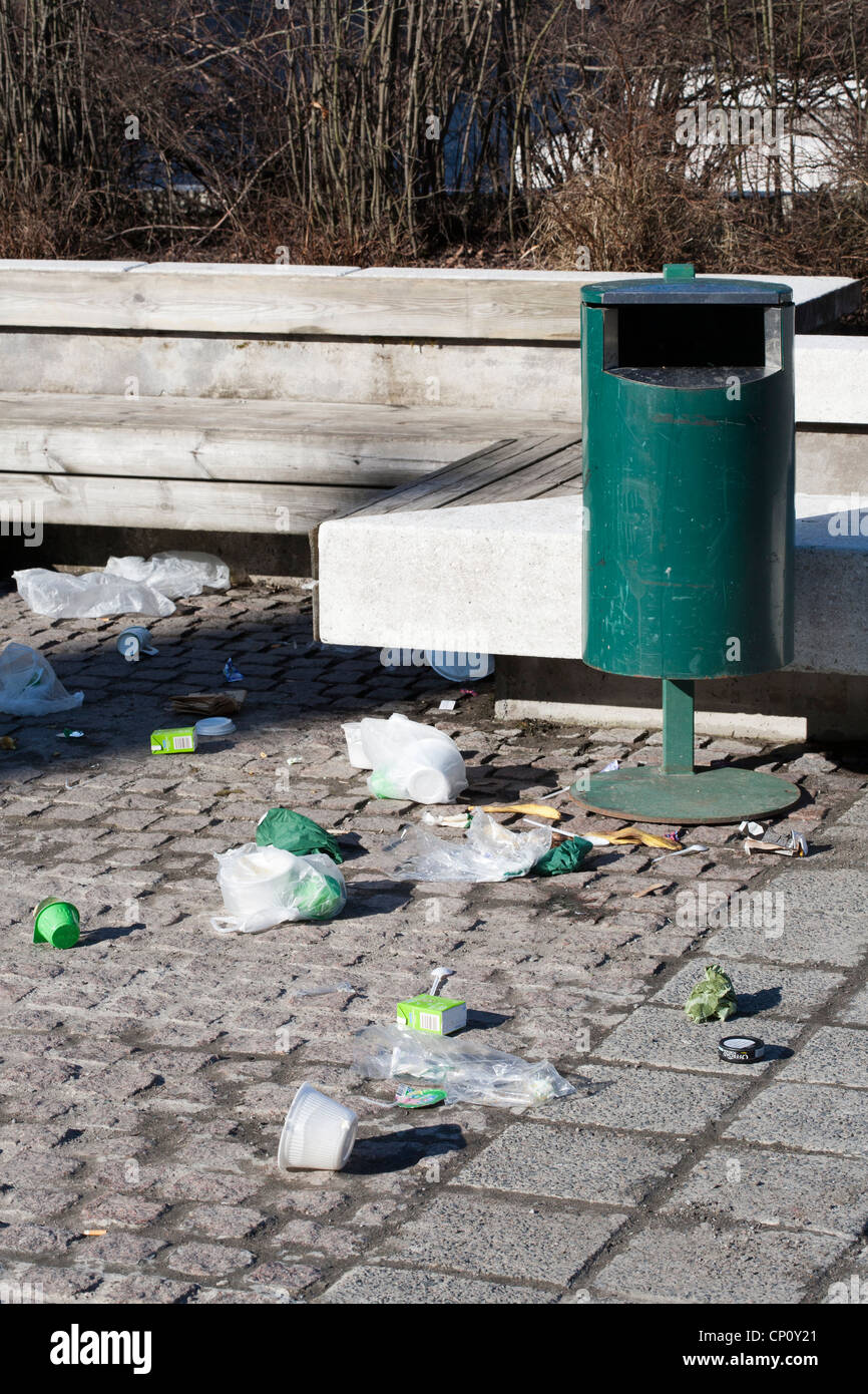 littered area with empty trashcan - Stock Image