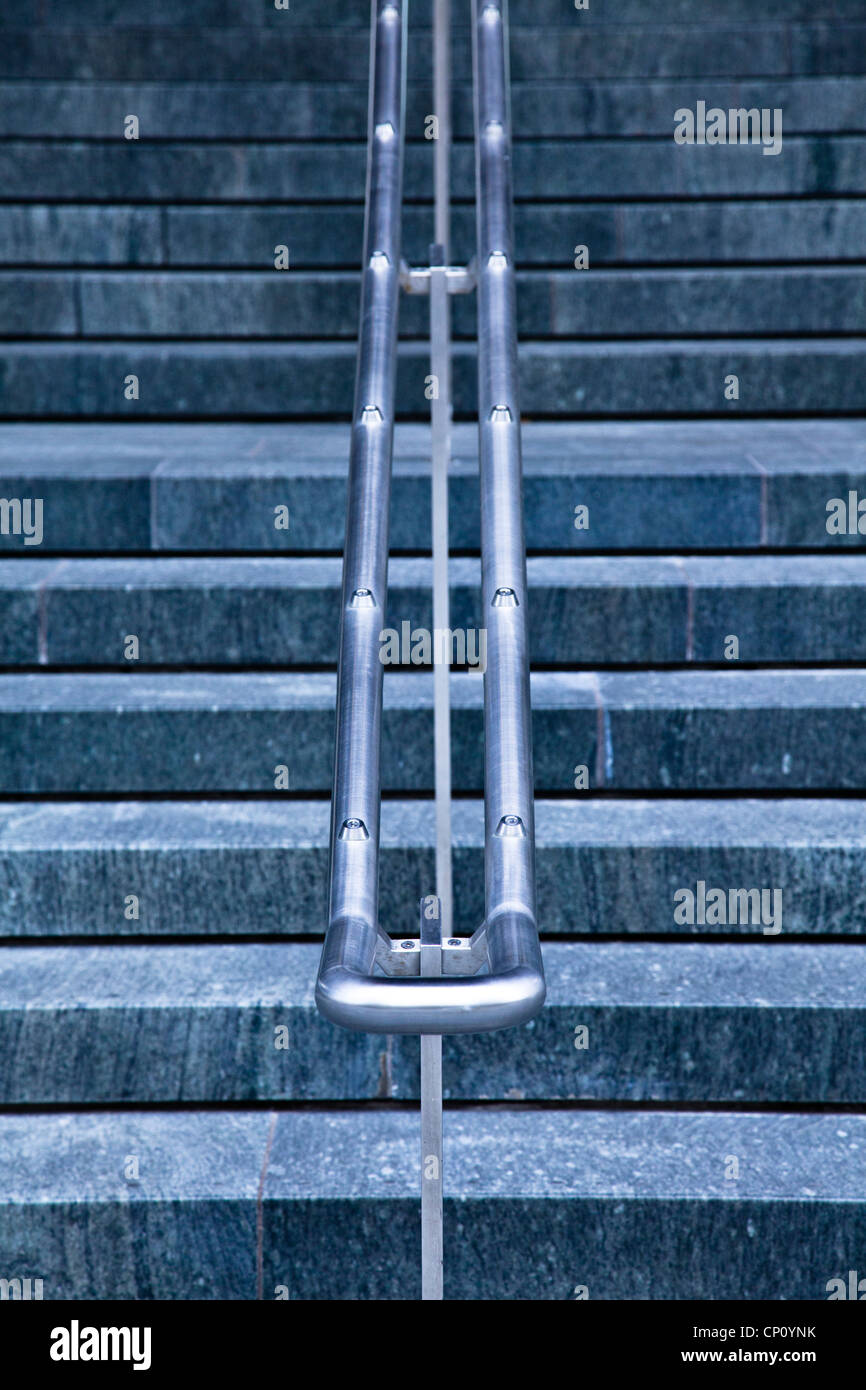 Symmetrical steel railings lead up a stone staircase in the City of London - Stock Image