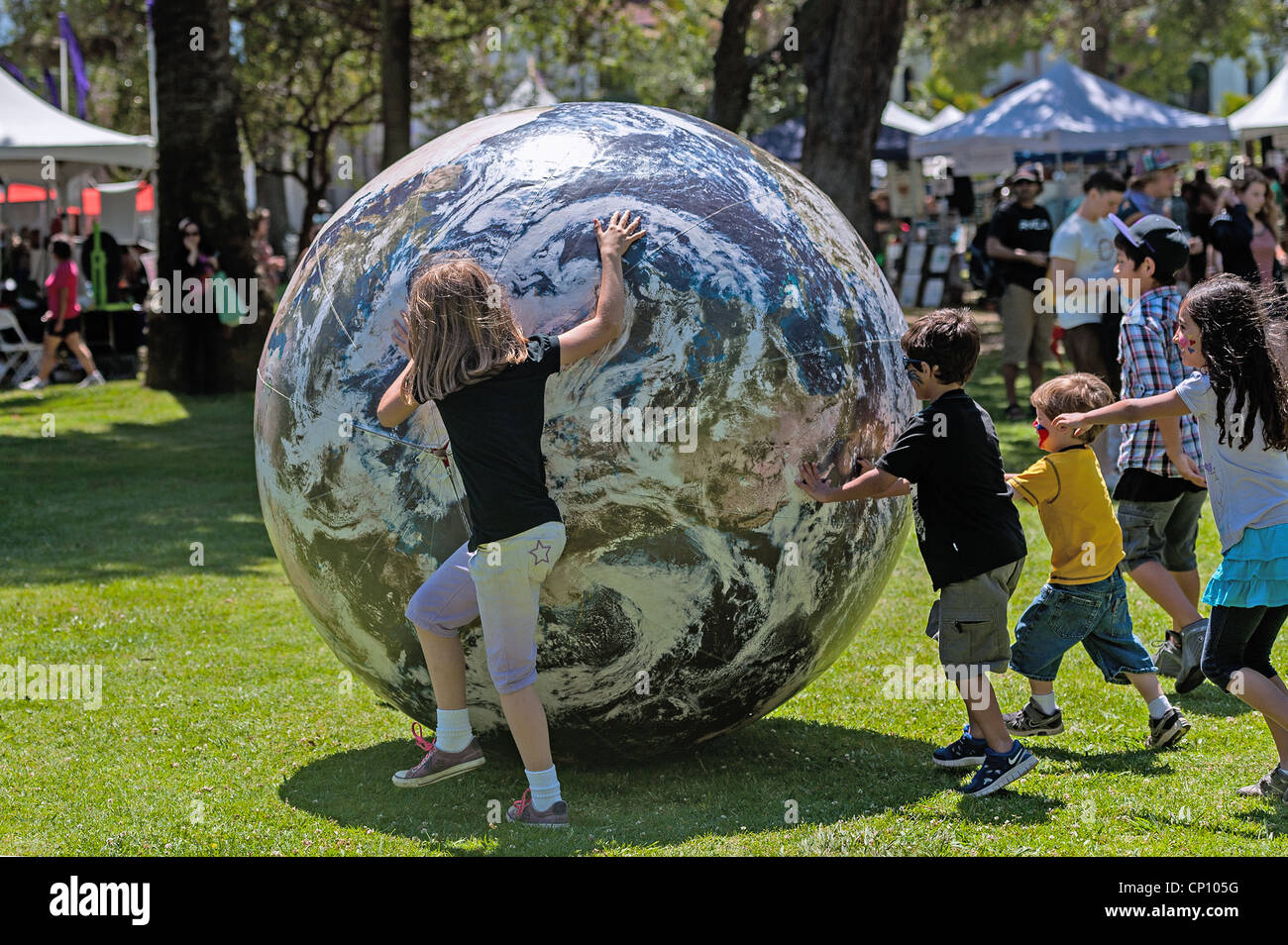 Children roll a giant 'planet Earth' inflatable ball at the annual  'Earth Day' happening at Alameda - Stock Image