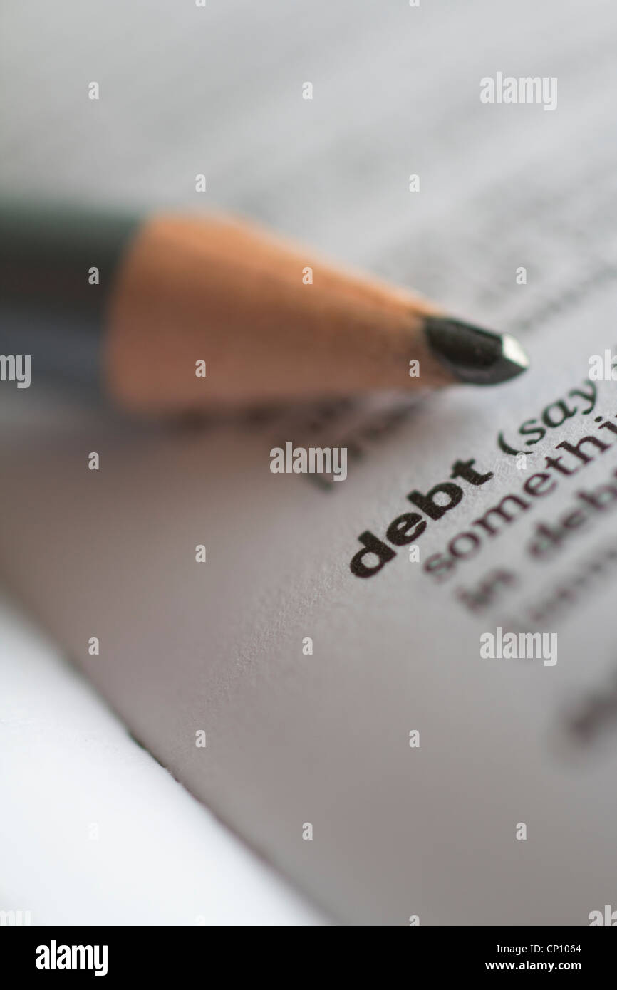 Debt the word debt in dictionary with pencil - Stock Image