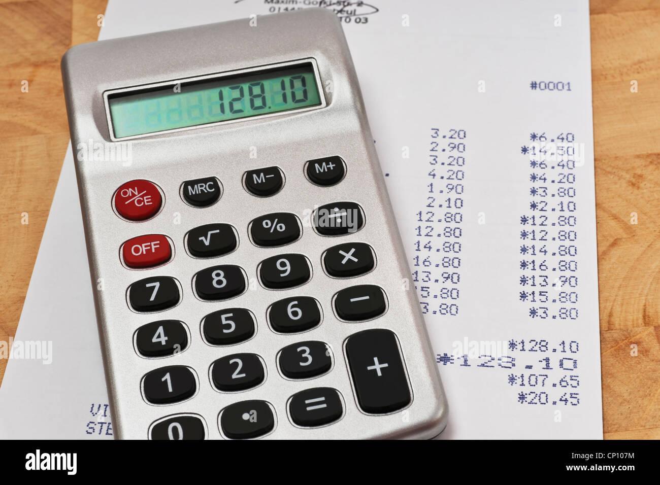 Ein Taschenrechner liegt auf einer Rechnung   A pocket calculator lies on an invoice. Stock Photo
