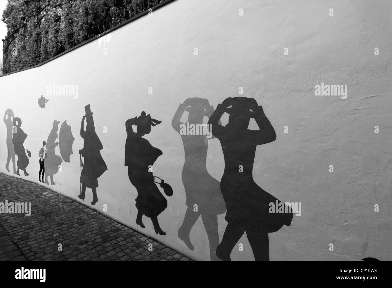 People walking, holding hats on a windy day. Mural in old twon Zurich. - Stock Image