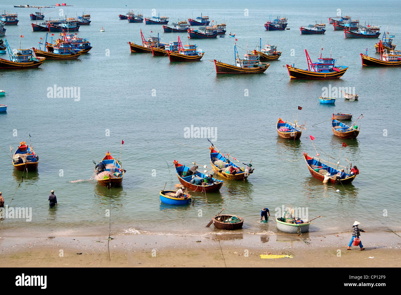 Fishing boats and thriving activity in the bay in Mui Ne, Vietnam. - Stock Image