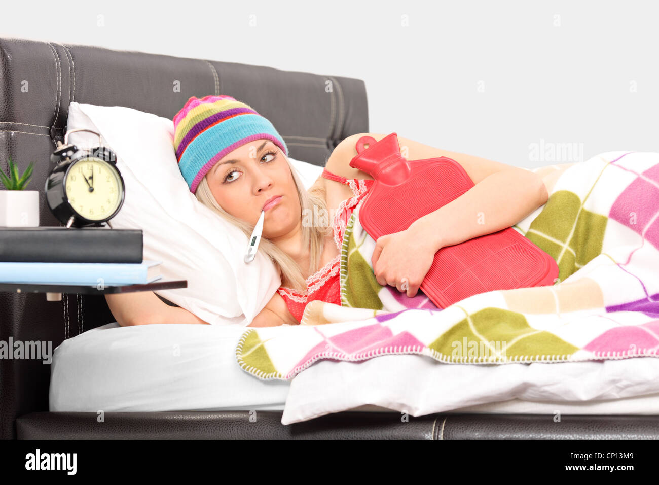 Ill woman in a bed holding a hot-water bottle and a thermometer in her mouth - Stock Image