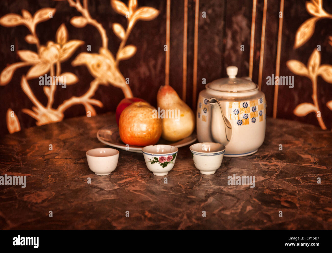 still life low key image of a tea pot cups and fruit - Stock Image