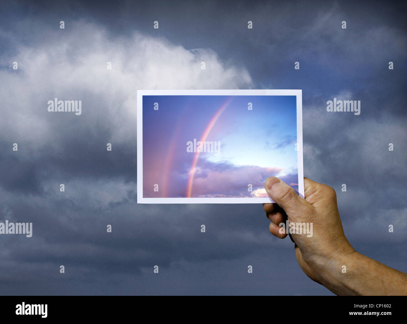 Hand Holding Photograph of Rainbow over Cloudy sky - Stock Image