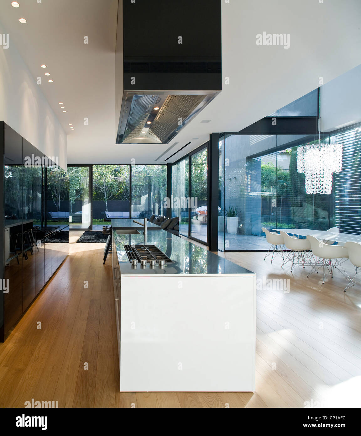 Interior of modern glass house. Open plan kitchen with island unit ...