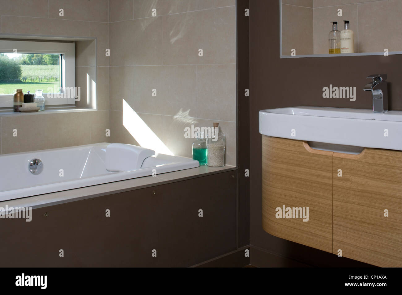 Dark brown bathroom with recessed bathtub in carbon neutral home in Crossway, Kent, England. - Stock Image