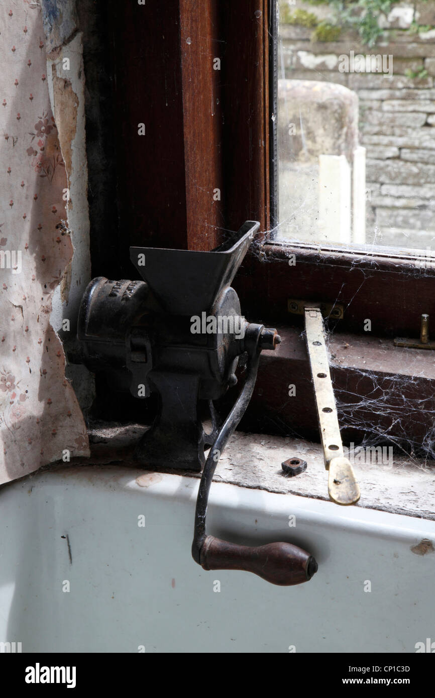 Meat grinder on windowsill of derelict pub, Craswall, Herefordshire, UK. - Stock Image