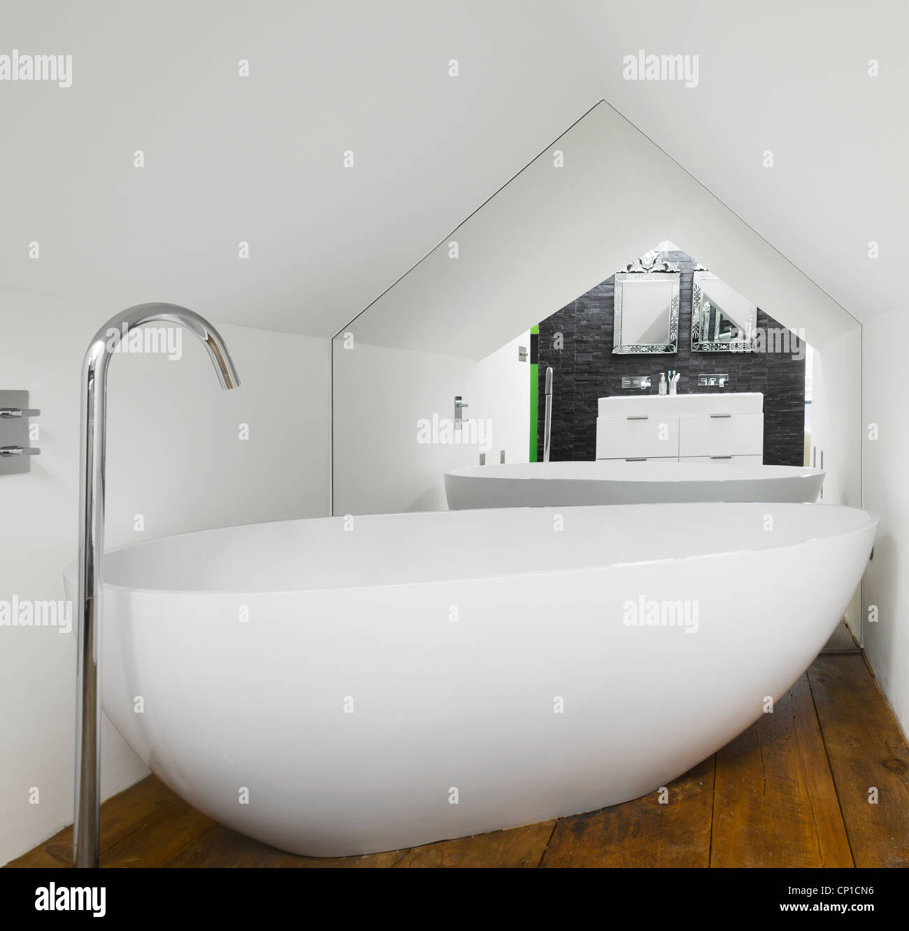 Bath under roof eaves of loft extension - Stock Image